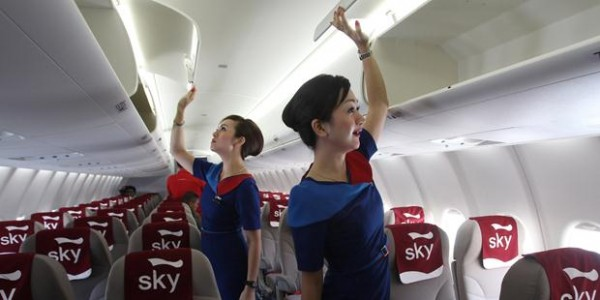 Sky Aviation's stewardesses shows to photographers the overhead luggage bin of a Sukhoi Superjet-100 during the unveiling ceremony of the first of the 12 jetliners purchased by the domestic airline at Halim Perdanakusumah airport in Jakarta, Indonesia, Thursday, Feb. 28, 2013. (AP Photo/Tatan Syuflana)