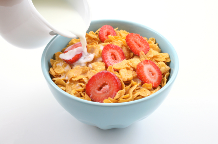 bowl of corn flakes with strawberry and jug of milk isolated on white